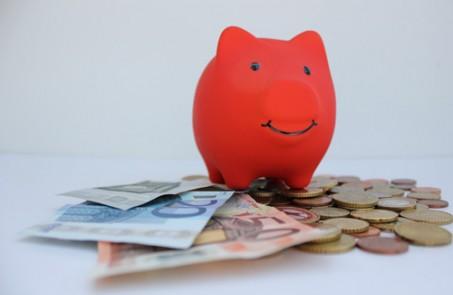 Rotes Sparkassenschwein auf Geldscheinen als Symbol für Sparkassenspenden.