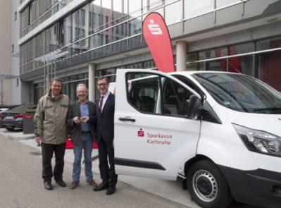 Michael Huber von der Sparkasse Karlsruhe übergibt den Kleinbus an die Vereinsvertreter der Sportjugend Vereinshilfe Karlsruhe.
