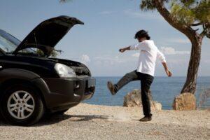 Mann tritt gegen seinen Mietwagen mit dem er liegengeblieben ist.