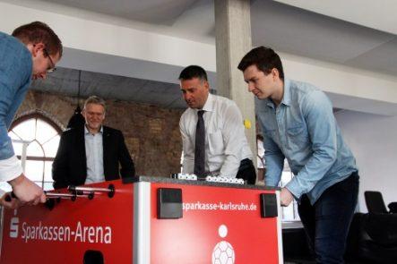 Drei Männer von der Firma CyberLab und Sparkassendirektor Marc Sesemann spielen am Tischkicker.